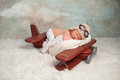 Newborn baby aviator boy studio portrait of an eight day old wearing an cap with goggles he is sleeping on a vintage inspired Royalty Free Stock Photography