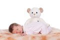 Newborn baby beautiful female in pink sleeping with bear Royalty Free Stock Photos