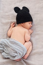 Newborn baby in black mouse hat soft image of cute sleeping on grey background focus on ear close eye nose feets and back Royalty Free Stock Photos
