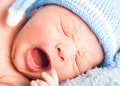 Newborn baby in a blue cap yawning Stock Photography