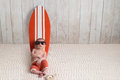 Newborn Baby Boy Leaning on Surfboard Royalty Free Stock Photo