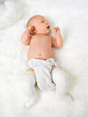 Newborn baby boy with legs wrapped in bandage full length of on fur blanket Stock Photo