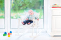Newborn baby boy in rocking chair next window Royalty Free Stock Photo