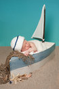 Newborn baby boy sailor sleeping in a sailboat one week old wearing white and blue hat he is little surrounded by sand and Royalty Free Stock Images