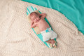 Newborn baby boy sleeping on a surfboard tiny he is wearing crocheted boardshorts and sandals Stock Image