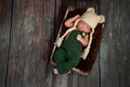 Newborn baby boy wearing a bear hat portrait of crocheted green overalls and he is sleeping in an old wooden crate shot in the Stock Images