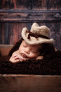 Newborn baby boy wearing a cowboy hat day old crocheted cowbow and sleeping on his stomach in wooden crate shot in the studio on Stock Photos
