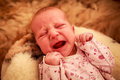 Newborn baby cries on woolen pillow in childish bodysuit closeup and makes wry face round Stock Photos