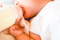 Newborn baby eating milk from the bottle. Royalty Free Stock Photo