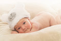 Newborn baby in funny hat portrait of awake boy wearing bear shape on soft beige cover Stock Photos