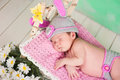 Newborn baby girl in a knitted hare costume sleeping on a wooden crib birch Royalty Free Stock Photo