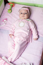 Newborn baby girl is laying in bed and wearing with pink clothes Royalty Free Stock Photos