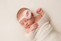 Newborn baby girl with light pink flower headband a portrait of a beautiful day old wearing a she is swaddled and sleeping on her Royalty Free Stock Photo