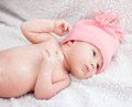Newborn baby girl with pink hat lying on white blanket Royalty Free Stock Image
