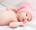 Newborn baby girl with pink hat lying on white blanket Stock Photos