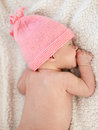 Newborn baby girl with pink hat lying on white blanket Royalty Free Stock Photos