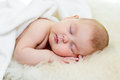 Newborn baby girl sleeping on fur bed Stock Photo