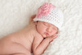 Newborn baby girl wearing a crocheted hat an day old sleeping white with pink flower she is sleeping on her stomach on white Royalty Free Stock Photo