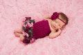 Newborn baby girl wearing a crocheted romper an overhead view of sleeping maroon headband and she is sleeping on her back on Stock Images