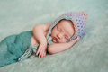Newborn baby girl wearing a pixie hat portrait of day old sleeping she is multi colored crocheted and wrapped in gauzy teal Royalty Free Stock Photography