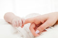 Newborn baby grasping her mother's finger. Child care, parent love. Royalty Free Stock Photo