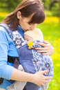 Newborn baby and mother outdoors walking with sling. Royalty Free Stock Photo