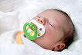 Newborn baby with pacifier sleeping on a white blanket Stock Photography
