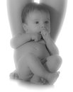 Newborn baby sitting by mom s feet isolated in black and white Royalty Free Stock Photo