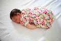 Newborn baby sleeping in fetal position girl on bed Stock Photos
