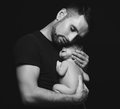 Newborn baby sleeping in his arms of father on dark Royalty Free Stock Photo