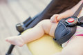 Newborn baby sleeping in stroller outdoors. Small baby barefoot with copy space