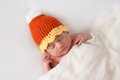 Newborn baby wearing a halloween candy corn hat girl themed costume she is sleeping on her back on white blanket Stock Photo