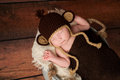 Newborn baby wearing a monkey hat crocheted and sleeping in galvanized bucket shot in the studio with rustic wood background Stock Photos