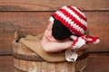 Newborn baby wearing a pirate hat and eye patch one week old boy crocheted red white black he is sleeping in rustic wooden Royalty Free Stock Photography