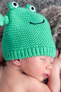 Newborn with beanie headshot portrait of adorable baby boy week old sleeping on his belly and wearing a colourful green frog Stock Image