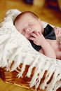 Newborn boy wearing bow tie laying in the basket Stock Images