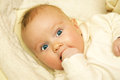 Newborn european baby girl boy wondering with finger in mouth Royalty Free Stock Photo