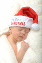 Newborn infant and first christmas in a red santa hat Royalty Free Stock Photography