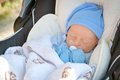Newborn napping in stroller a baby a wearing a blue hat and mittens Royalty Free Stock Image