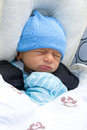 Newborn napping in stroller a baby a wearing a blue hat and mittens Royalty Free Stock Photos