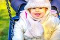 Newborn swing baby smile winter fun play park outdoor playground Royalty Free Stock Photo
