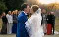 Newly married couple kissing in front of happy guests at park portrait Stock Image