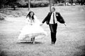Newly married couple running in park black and white photo of Stock Images
