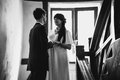 Newly married couple standing on stairs black and white photo of against big window Stock Photos