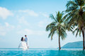Newly married couple after wedding in luxury resort. Romantic bride and groom relaxing near swimming pool. Honeymoon. Royalty Free Stock Photo