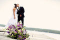 Newly wed couple together married people kissing with a bouquet of flowers in the foreground Royalty Free Stock Photography