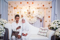 Newly wedded couple posing malay in an indoor portraiture Stock Photo