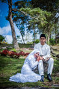 Newly wedded couple posing malay in an outdoor portraiture Stock Images