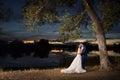 Newlywed couple by lake at sunset Royalty Free Stock Photo