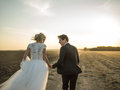 Newlywed couple dynamic picture running on the field holding hands at sunset Stock Photography